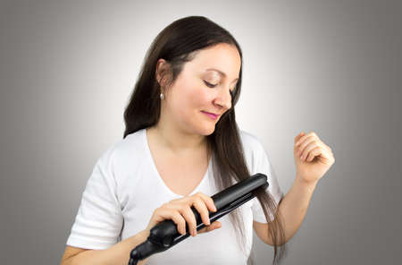 flat iron: happy woman using flat iron to straigh her hair