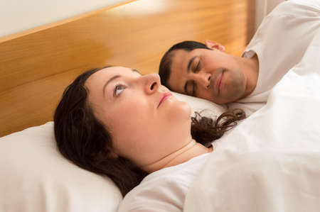 sleeplessness: portrait of couple in bed while woman with sleeplessness  thinking on her preoccupations while the husband sleep placidly