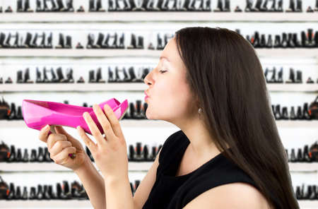 sexual selection: Attractive woman giving a kiss pink heeled shoes in the shoe store Stock Photo