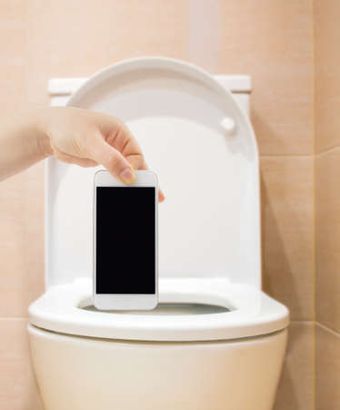 obsolescence: man throwing the smartphone to the toilet
