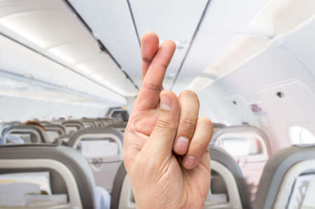 thumbs: hand crossing the fingers like symbol of superstition to have good luck at the indoor of the plane