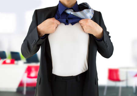 underneath: businessman ripping open his shirt and exposing a costume underneath Stock Photo