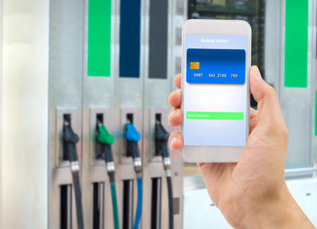hand holding the phone with mobile wallet to pay online at the gas station