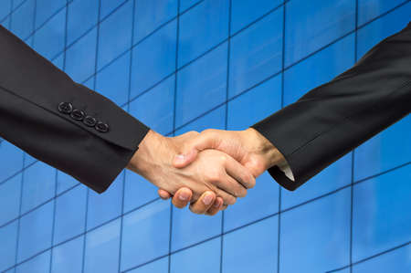 deal in: Business people shaking hands over a deal in office