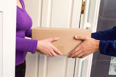 deliver: friendly delivery man delivering a package to a home Stock Photo
