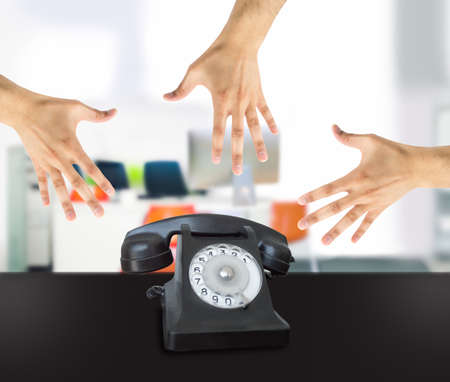 picks: Group of hands grabbing an old phone in the office Stock Photo