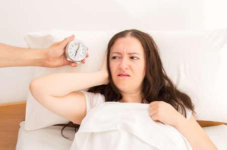 pareja en la cama: marido acercarse despertador para despertar a su esposa Foto de archivo