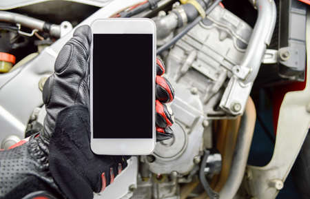 biker: biker man calling a mechanic with the phone