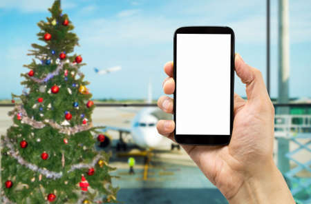 jesus christ christmas: Hand holding mobile smart phone with connect wifi on the airport on Christmas