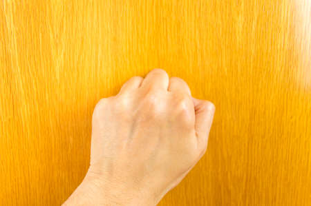 knocking: view of hand knocking the wooden door Stock Photo