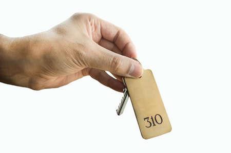 llaves: huésped con la llave de la habitación del hotel aislado en el fondo blanco Foto de archivo