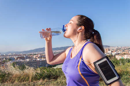 tomando agua: thirsty sport runner resting taking a break with water bottle drink outside