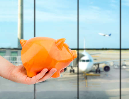 hand holding the piggy bank at the lounge airport Reklamní fotografie