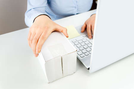 carrying box: woman with a laptop on the desk and holding a package Stock Photo