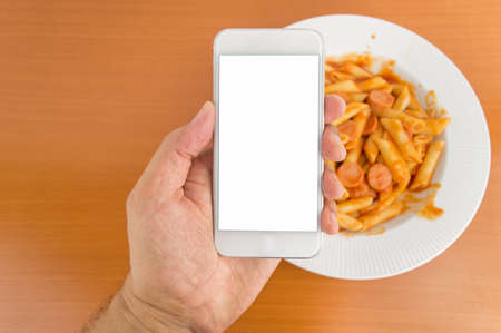 food photography: man holding smartphone making food photography to the meal at the table Stock Photo