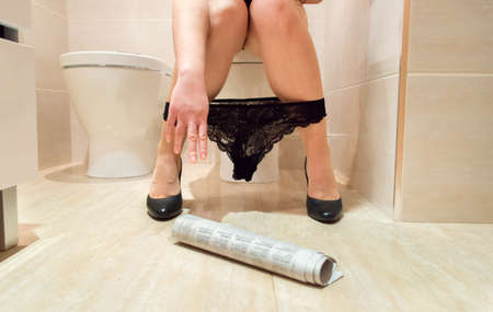 constipated: woman at the toilet trying to catch the newspaper on the floor