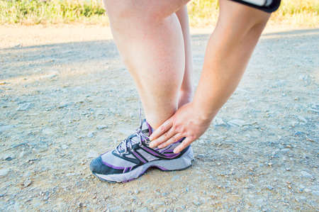 calf strain: athlete runner touching the foot with pain due to sprained ankle