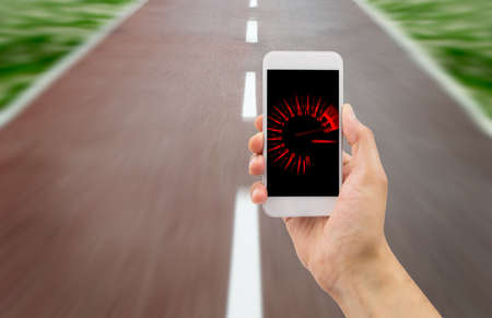 mobile internet: hand holding the smartphone with tachometer speed in the screen over the road in background Stock Photo