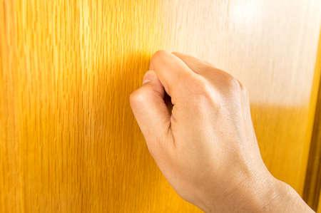 tocar la puerta: vista de perfil de la mano golpeando la puerta de madera