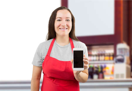 saleswoman: the smiling saleswoman in a coffee shop showing a smartphone