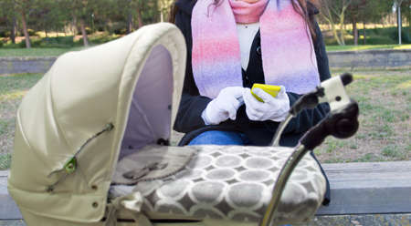 mother on bench: woman connected to social networks with a stroller at a park in winter Stock Photo
