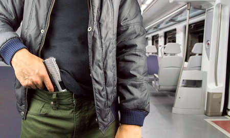 Angry man holding gun in the subway 스톡 콘텐츠
