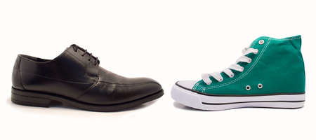 informal clothes: choice between formal shoe and sneaker by profile over white background Stock Photo
