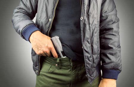 pandilleros: Primer plano de un terrorista armado con fondo gris Foto de archivo