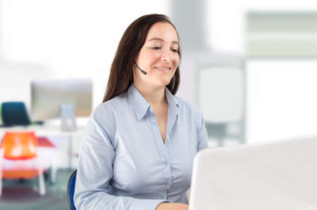 handsfree device: woman working at a call center operator sitting front the laptop and smiling Stock Photo
