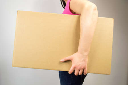 removals: young woman holding a box with copyspace on wite background Stock Photo