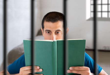 cellule prison: prisonnier de lire un livre dans sa cellule à la prison Banque d'images