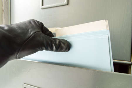 detail of a robber catching some files from the archive like symbol of industrial espionage Stock Photo