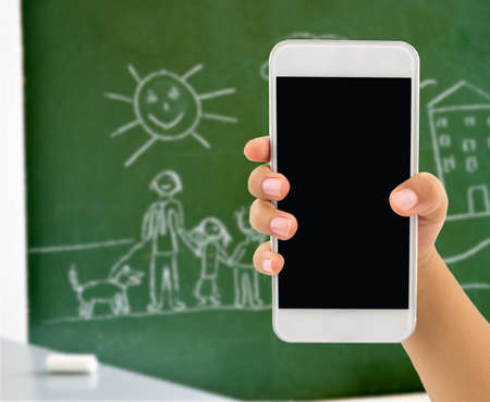 otras palabras clave: hand of child is holding a modern smartphone with blackboard and a drawing of a child on the background Stock Photo