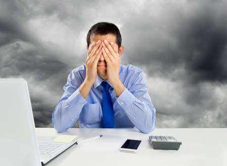 displeased businessman: man overwhelmed at the office with hands on his face