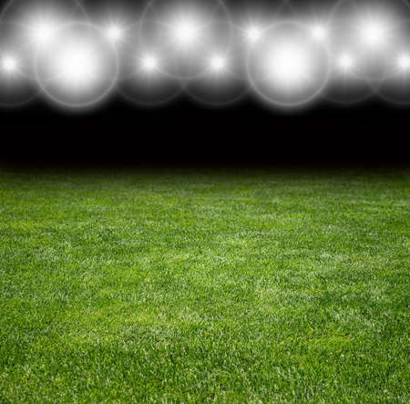 focuses: Green soccer field row of bright spotlights illuminated stadium in night Stock Photo