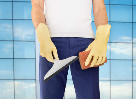 cleaning business: cleaning worker standing and holding squeegee and sponge to make the work at the outdoors of the building office
