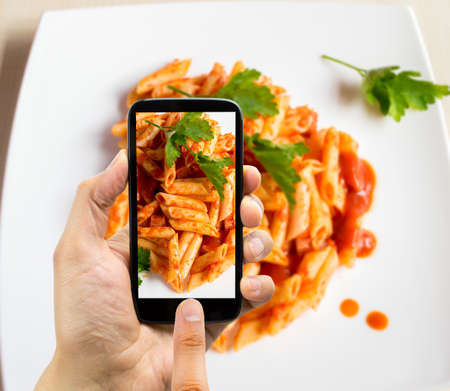 person: hand with smartphone photographing a plate of macaroni for upload to internet