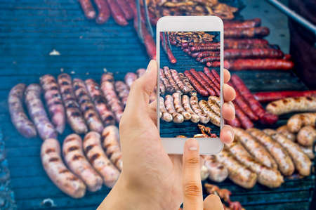 eating meat: Hands taking photo pork meat and sausages with smartphone Stock Photo