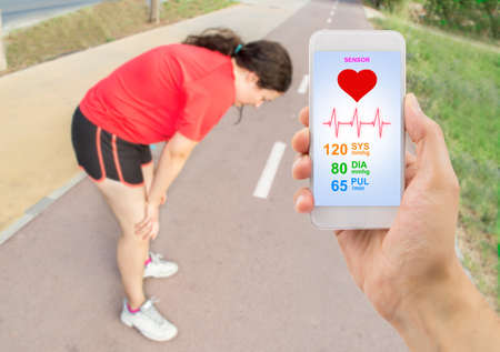 gasping: hand holding the smartphone with a healthy app and in background a woman gasping for air with her hands on her knees after a run .All screen content is designed by my and not copyrighted by others and created with digitizing tablet and image editor Stock Photo