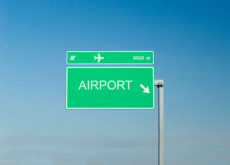 airport sign: Airport sign on a highway with blue sky in the background Stock Photo