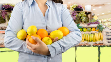 citric: portrait of woman holding in her arms citric fruits like lemons and oranges at the greengrocer on the background