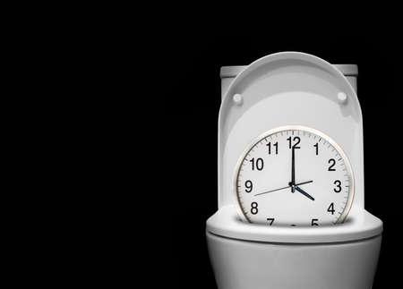 cuarto de ba�o: reloj en el wc como concepto de perder el tiempo sobre el fondo negro