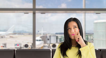 dreamlike: closeup of latin woman with her hand on the chin thinking a dreamlike at the airport lounge Stock Photo