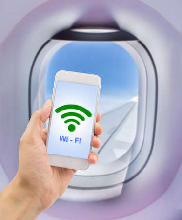 phone business: hand holding the smartphone with signal wifi at the indoor of the plane near the window