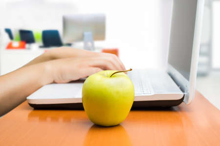 woman working with the laptop with a healthy apple Stock Photo
