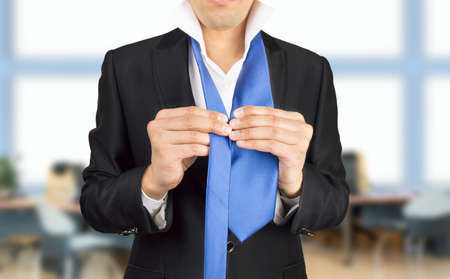 formal dressing: executive is preparing with suit and tie for a meeting at the office to impress