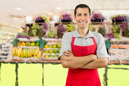 abarrotes: retrato de tendero en la tienda de frutas con los brazos de cruce