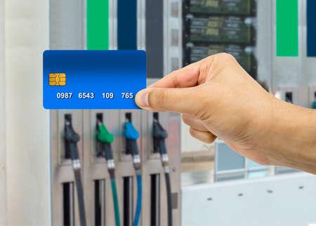 hand houden van de creditcard om een betaling bij het benzinestation te maken