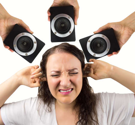 irritate: woman with hands in the ears disturbed by loud noise of the speakers