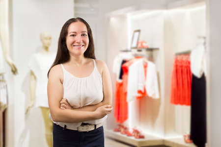 shopgirl: happy saleslady standing at the boutique